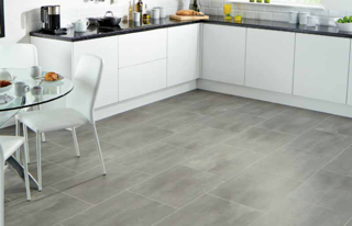 White kitchen with grey tiled flooring with white cabinets and black counter tops