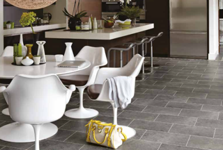 Grey kitchen with a grey tiled floor with white table and chairs and white and brown island