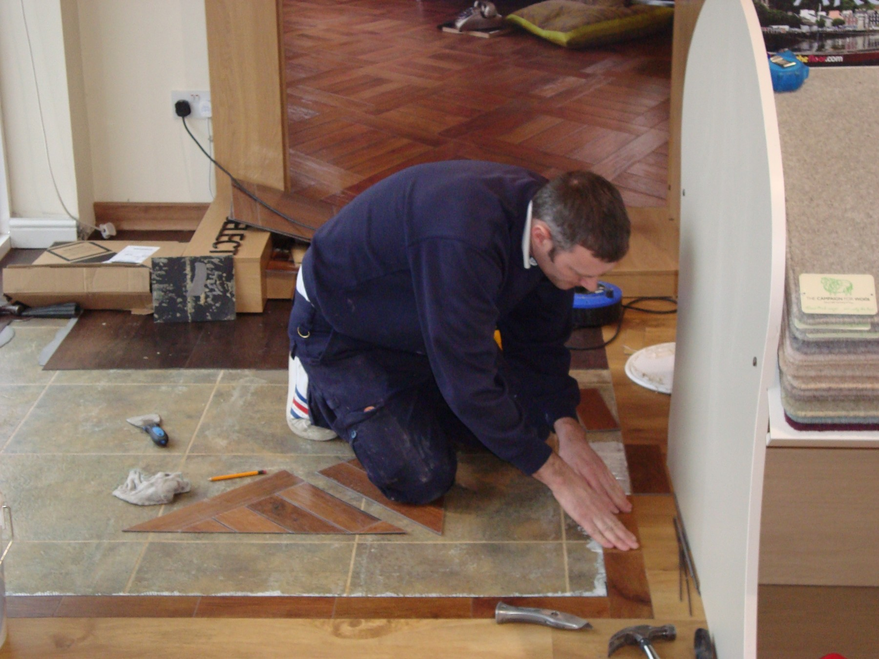 Workman in blue overalls laying flooring in a magnolia room