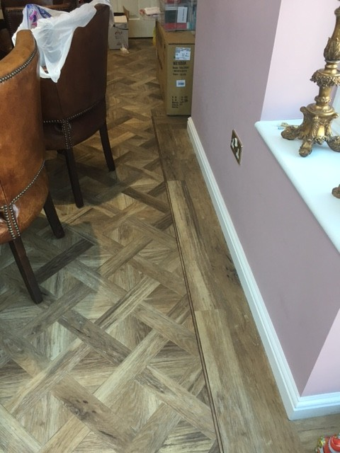 Pink room with wooden cross hatch flooring
