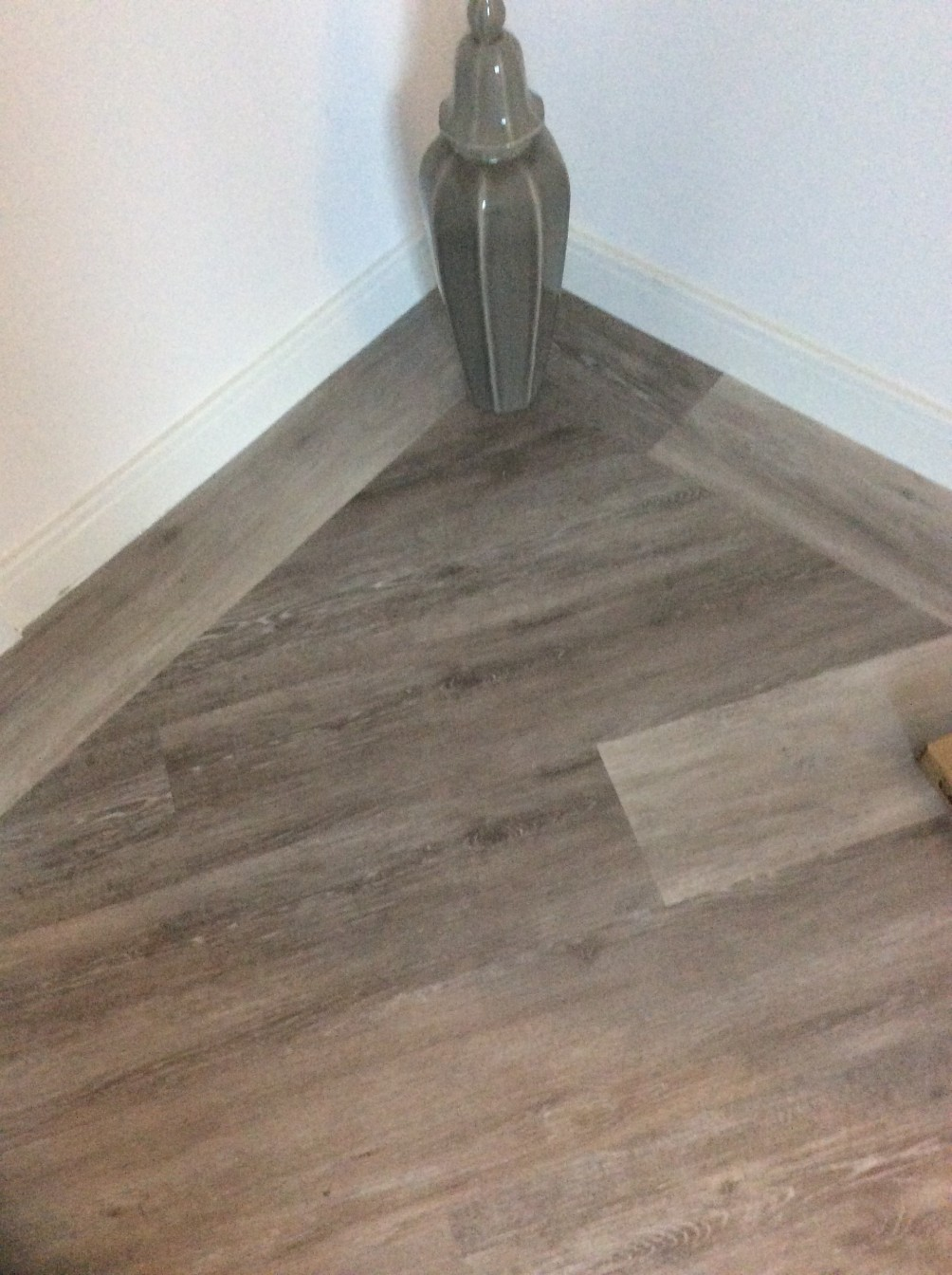 White room with a dark wooden patterned flooring