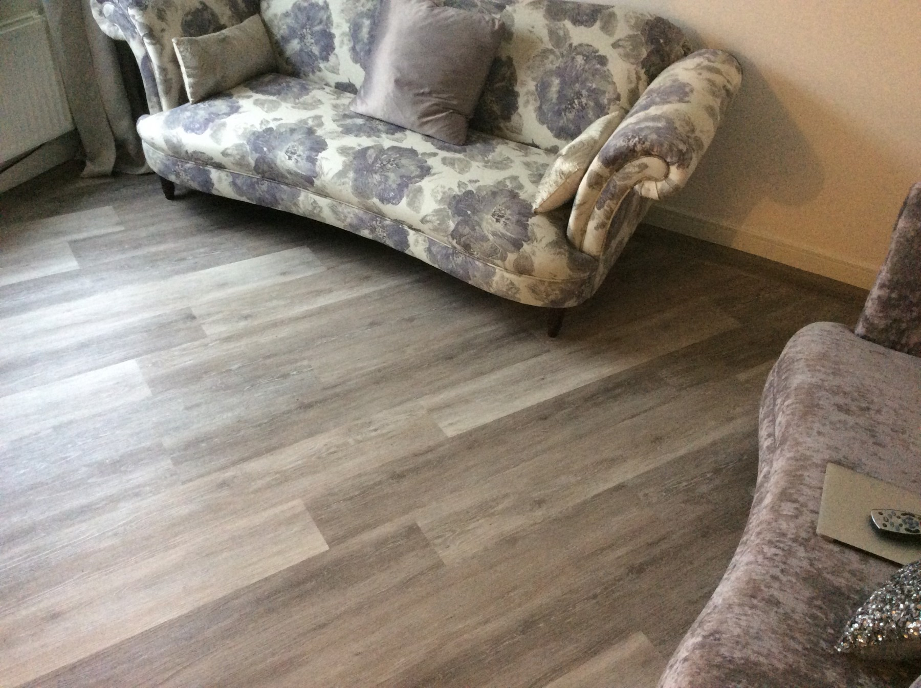 Cream room with dark wooden flooring and a patterned couch