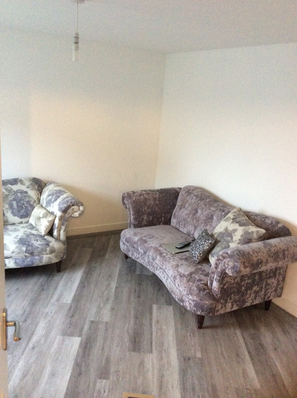 Cream room with velour couches and grey wooden flooring