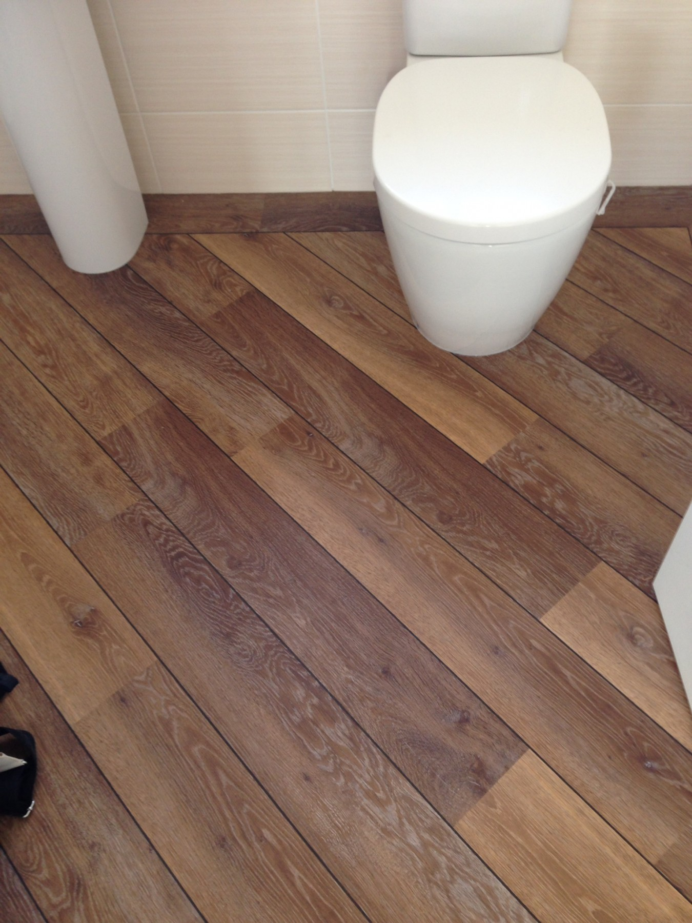 Cream tile room with a white toilet and dark wooden flooring