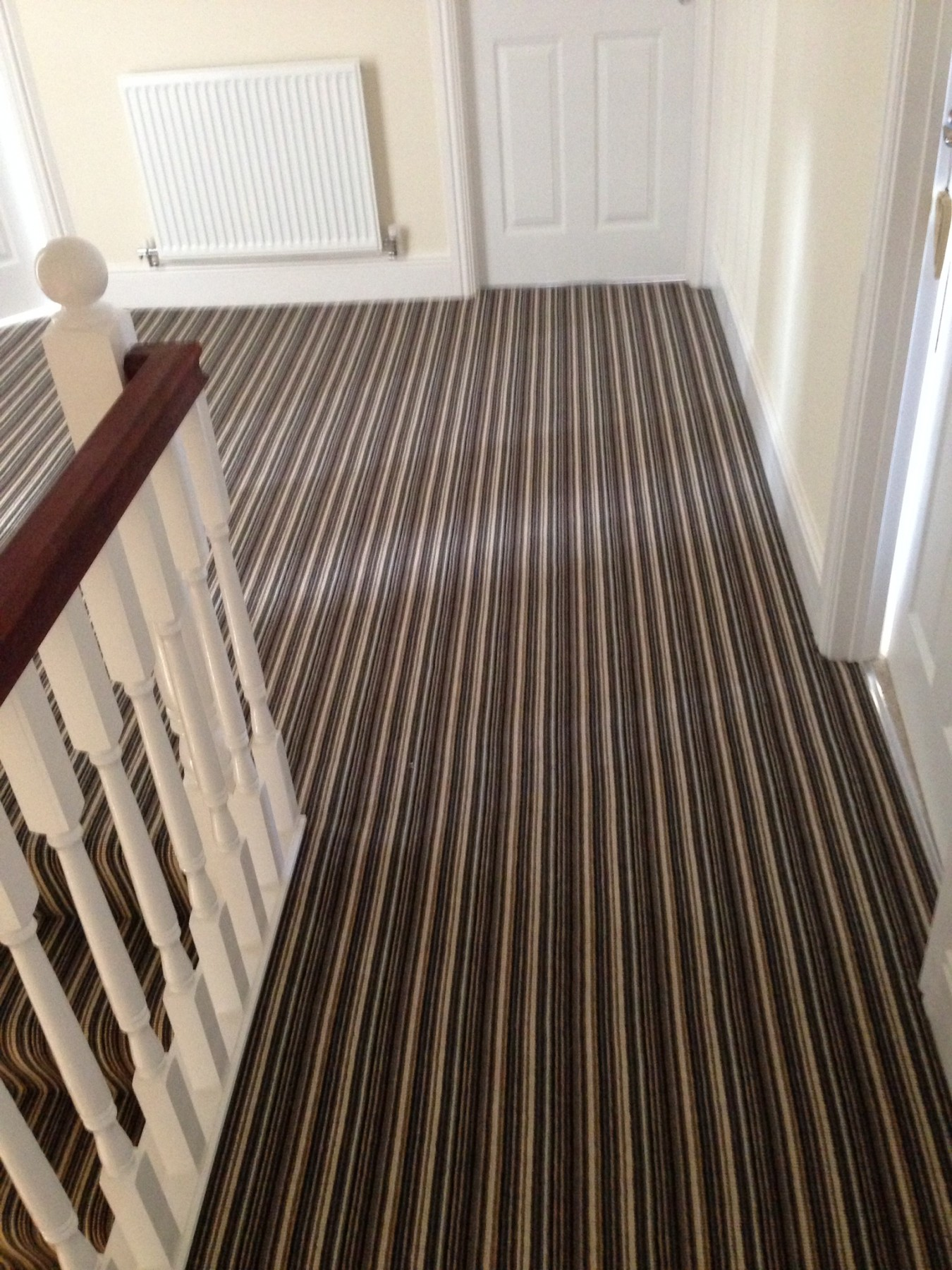Striped carpet on a large landing with cream walls