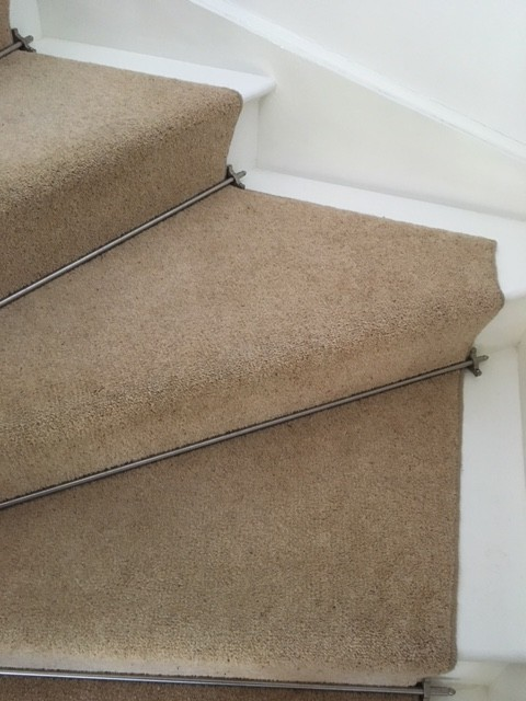 Cream carpets on a white corner stair case held in place by metal rods
