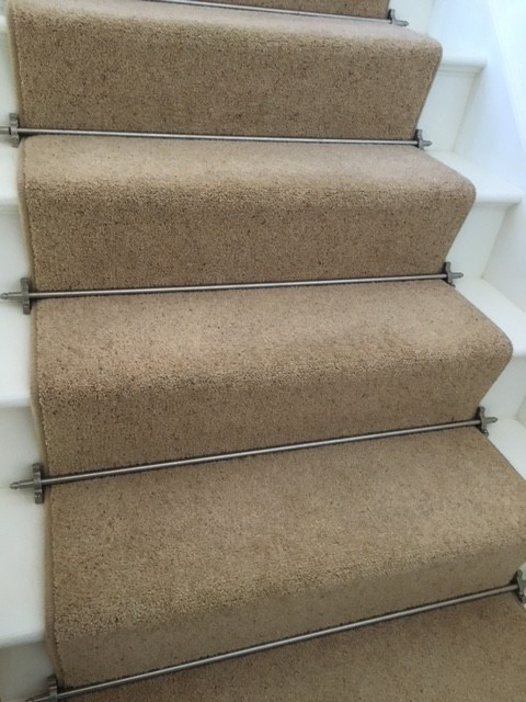 Cream carpet on white stairs held in place by metal rods