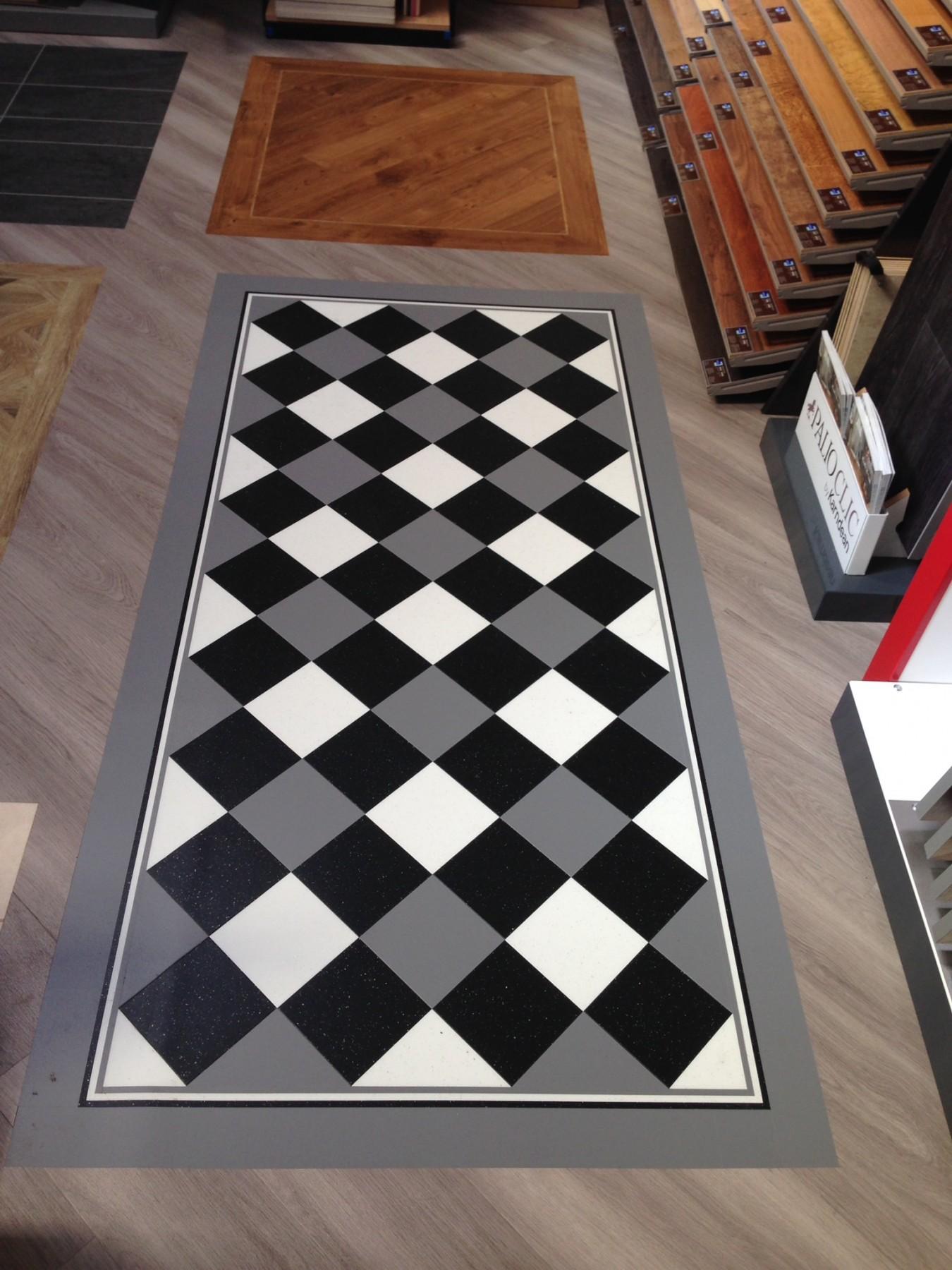 Grey flooring with a black and white patterned floor