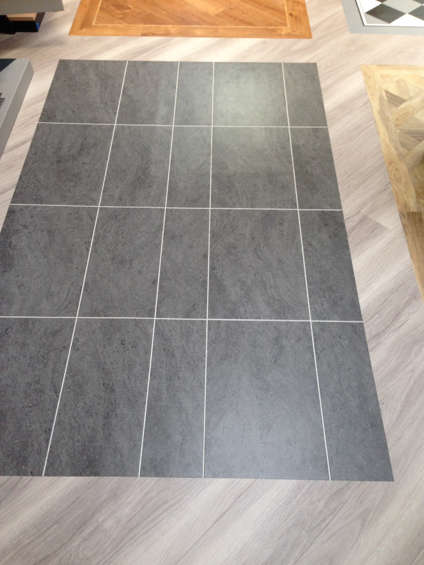 Light grey tile flooring with a dark grey tiling in the centre
