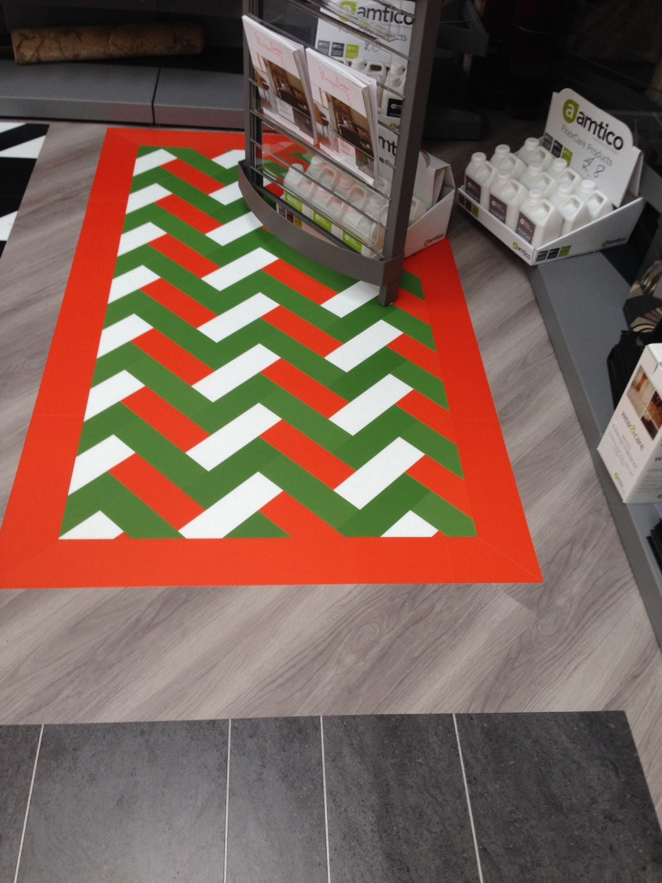 Grey flooring with a red white and green pattern