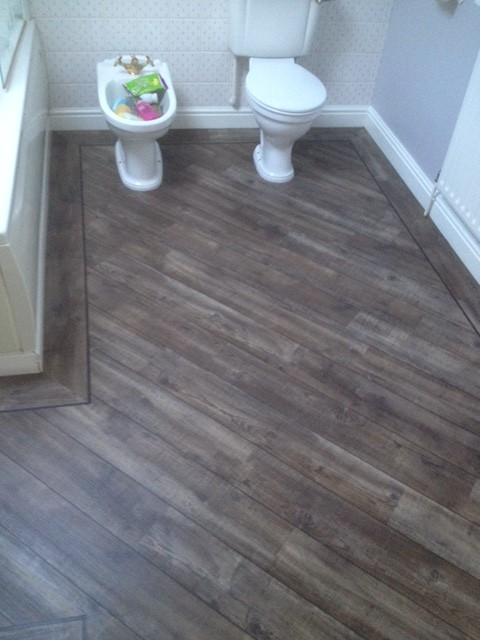 Bathroom with a toilet and bidet with dark wooden flooring