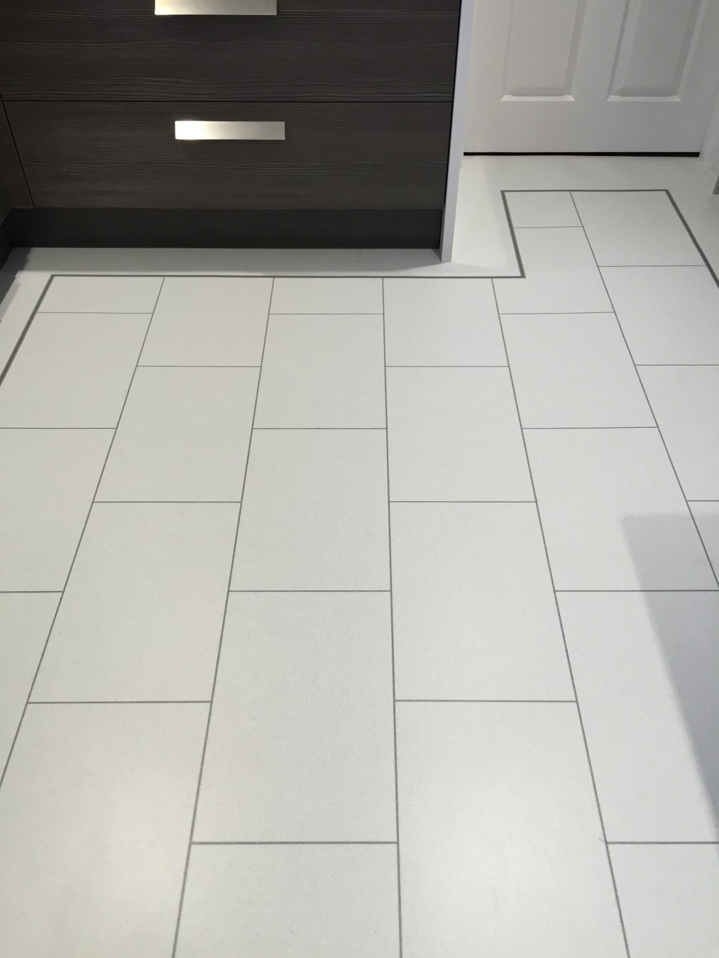 Bright room with white tile flooring black cabinets and a white door