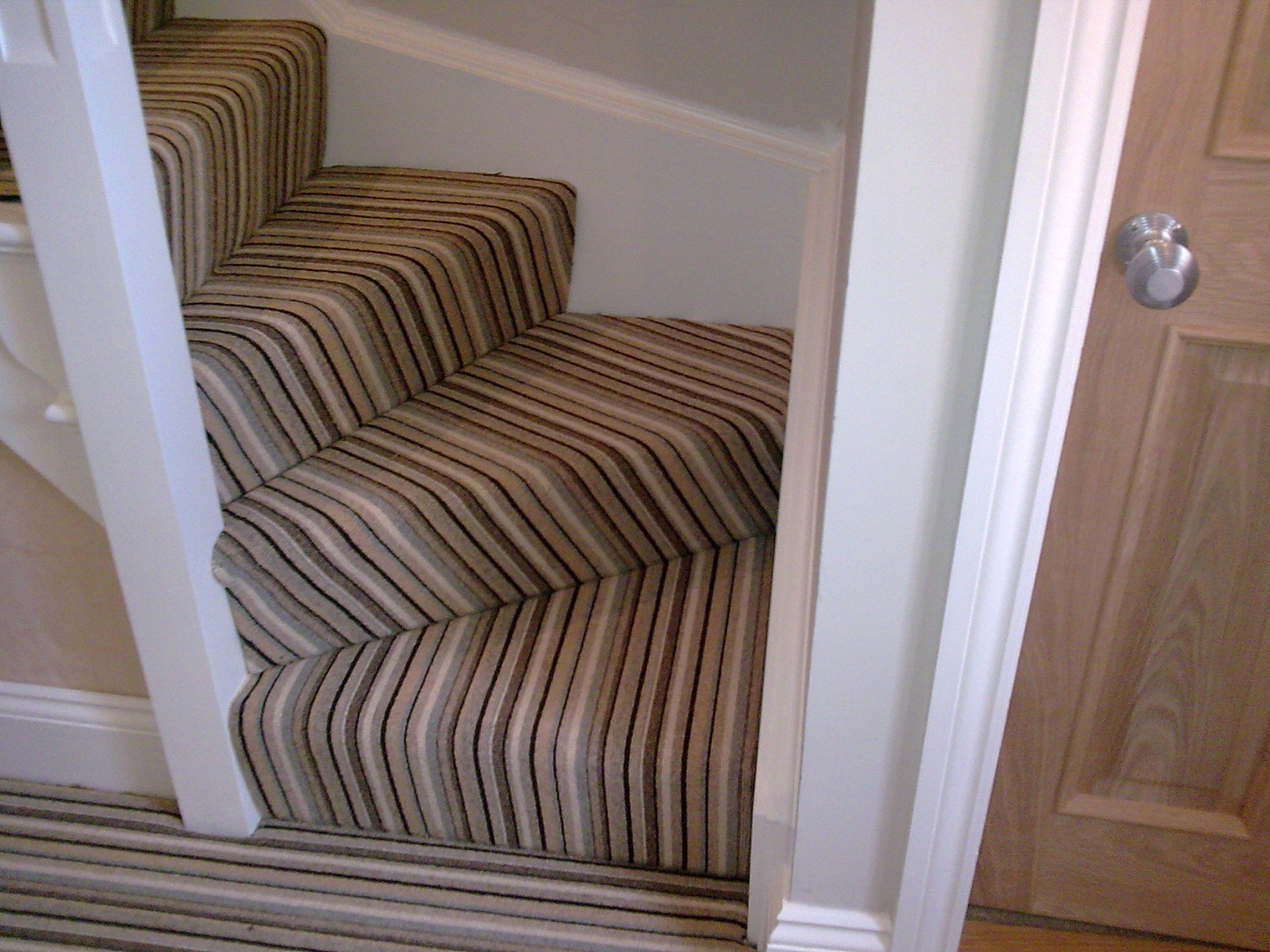 Corner staircase with a striped carpet matching the hallway