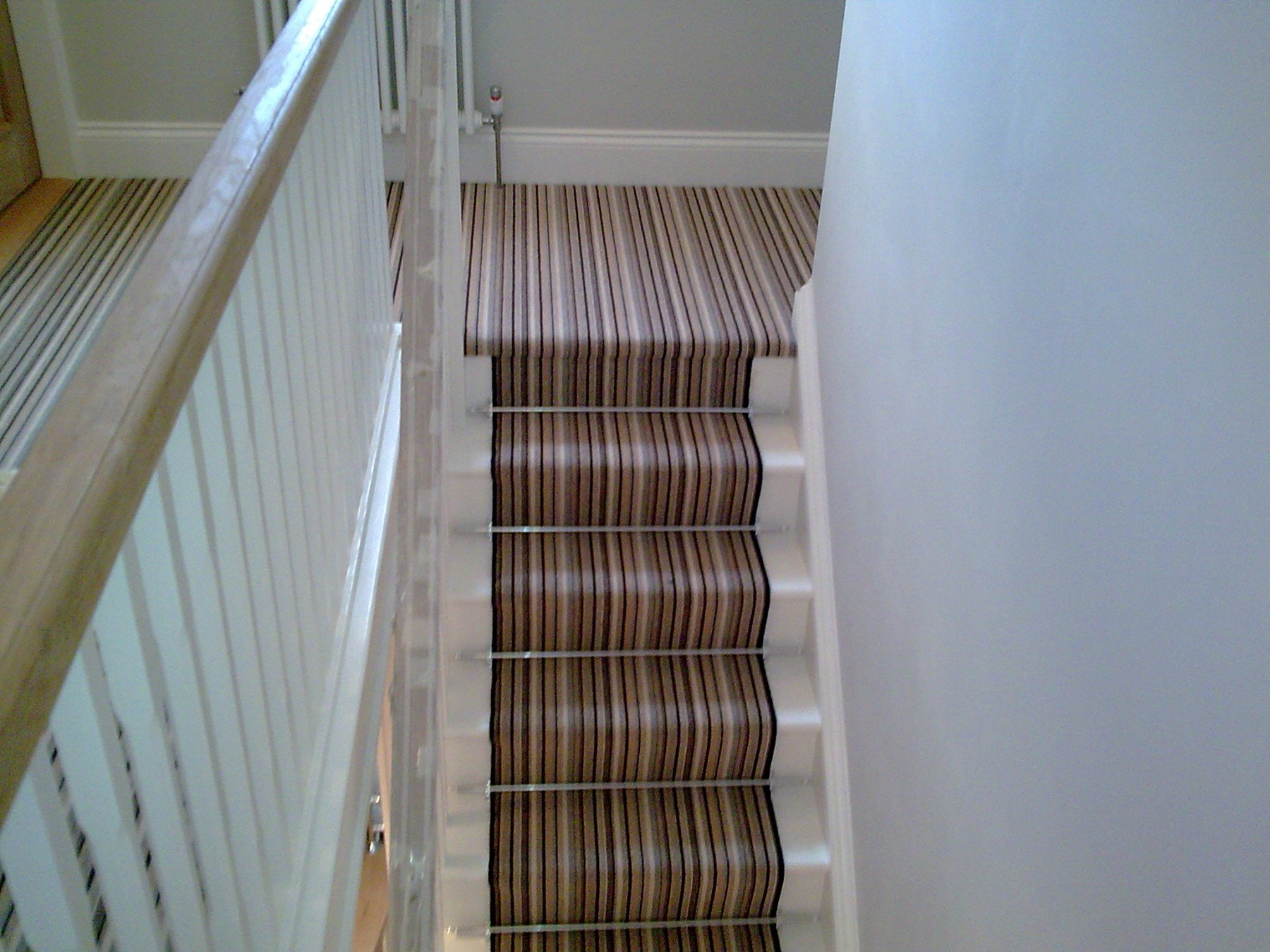 Striped carpet in a landing and up a staircase with grey walls
