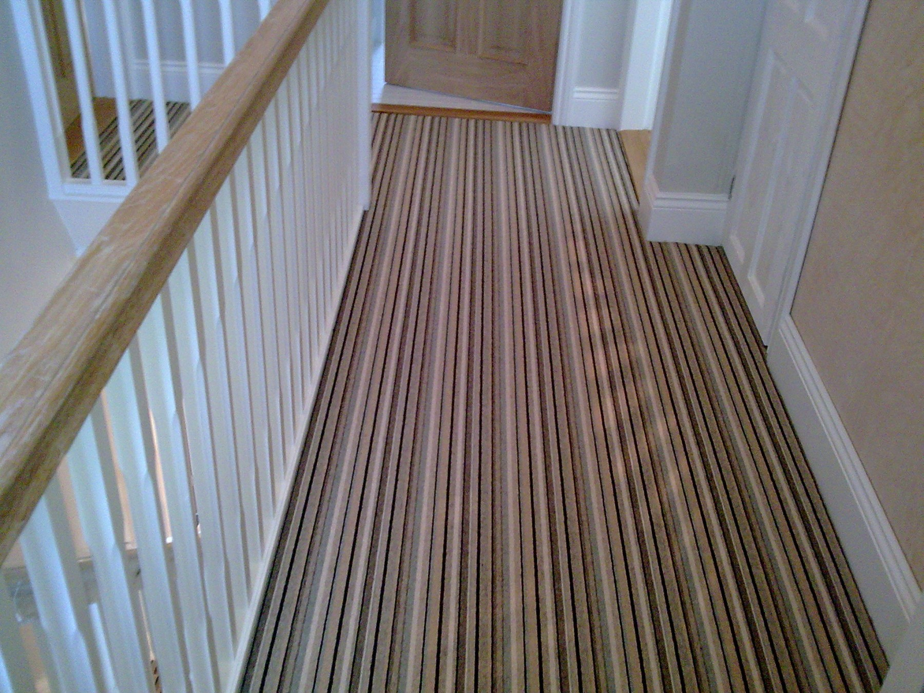 Striped carpet on a small landing with beige walls
