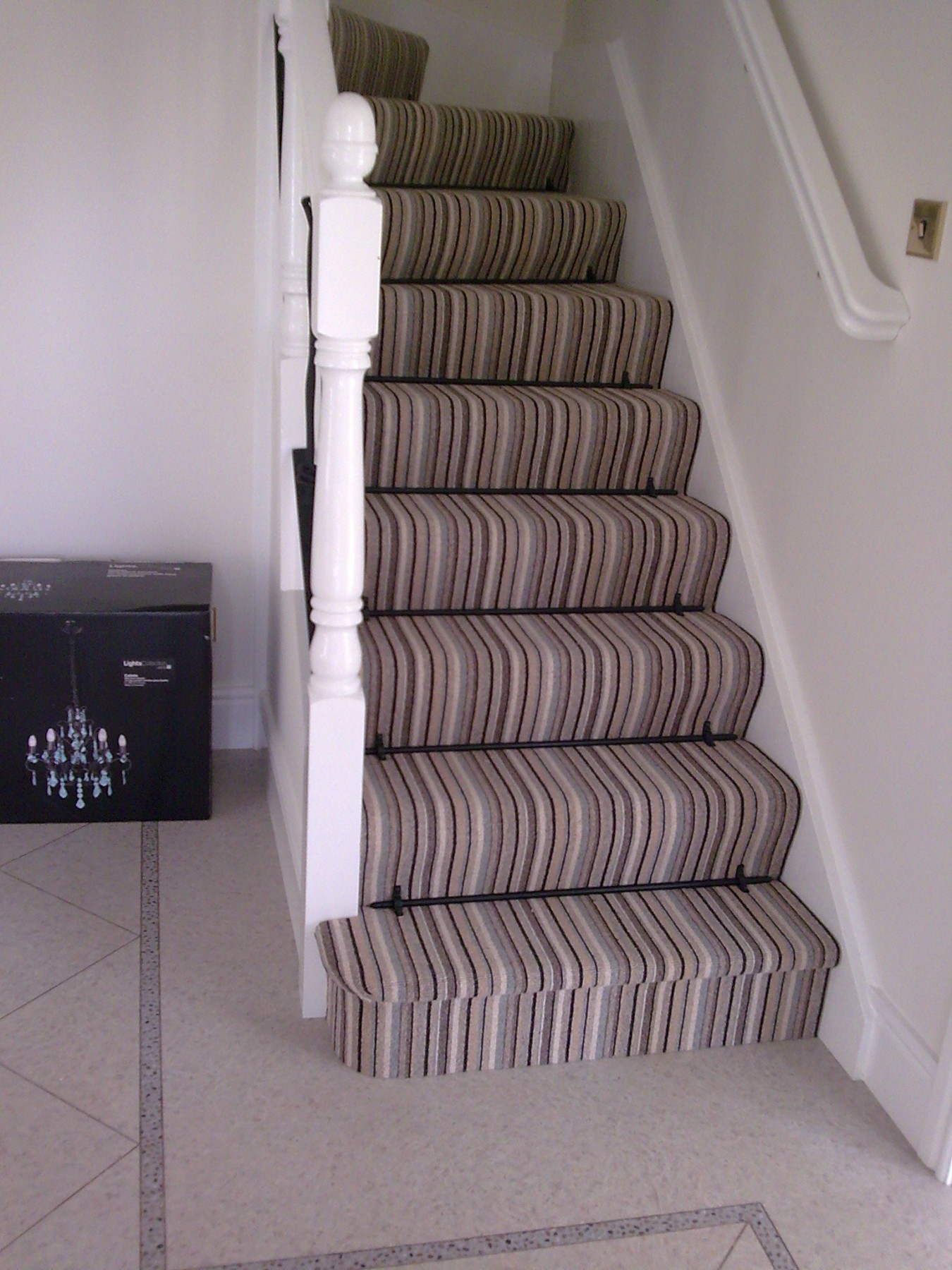 Staircase with striped carpet in a cream room