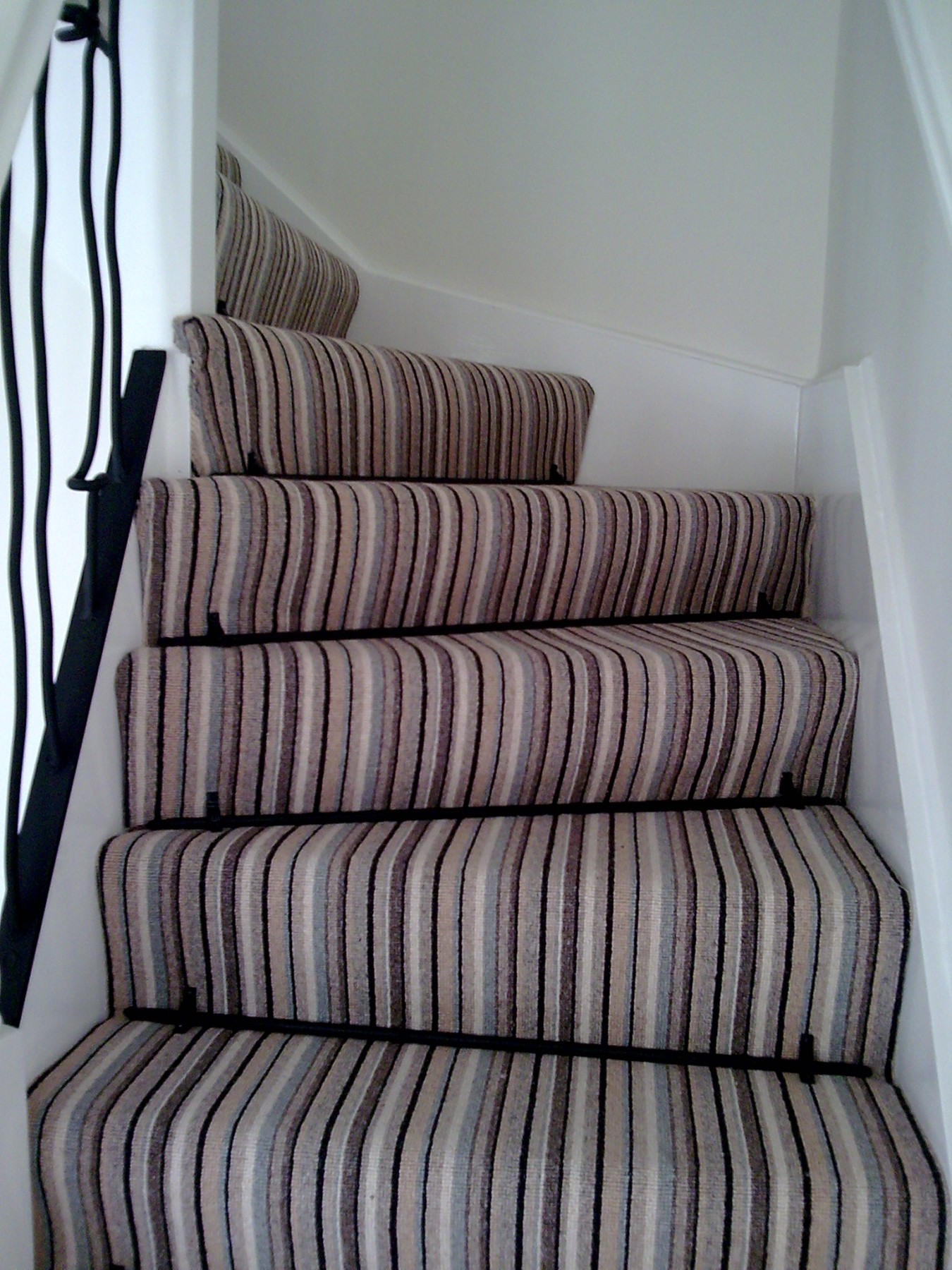 Corner staircase with a striped carpet