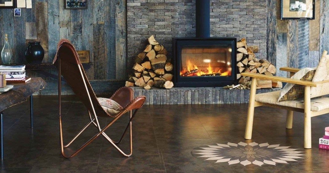 Wooden clad room with brown tiled flooring and a log burning fire with logs beside it