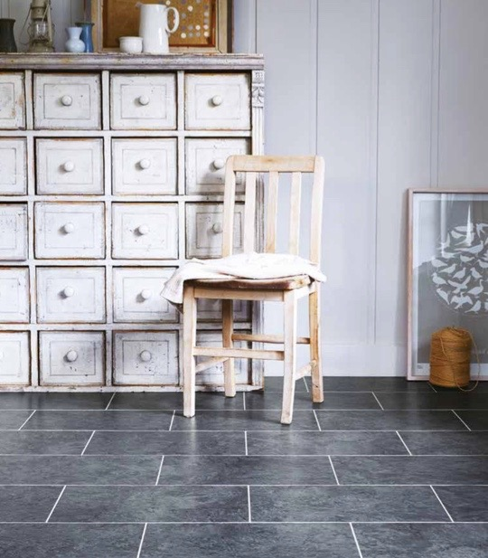 White room with black tiled floor with rustic wooden furniture