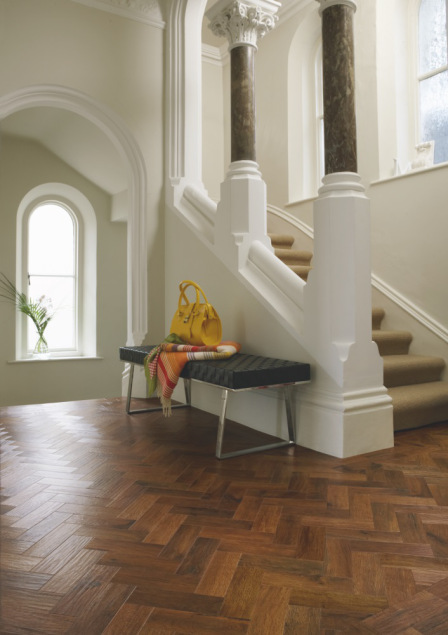 Large white hallway with columns and dark wooden chevron flooring with a black seat