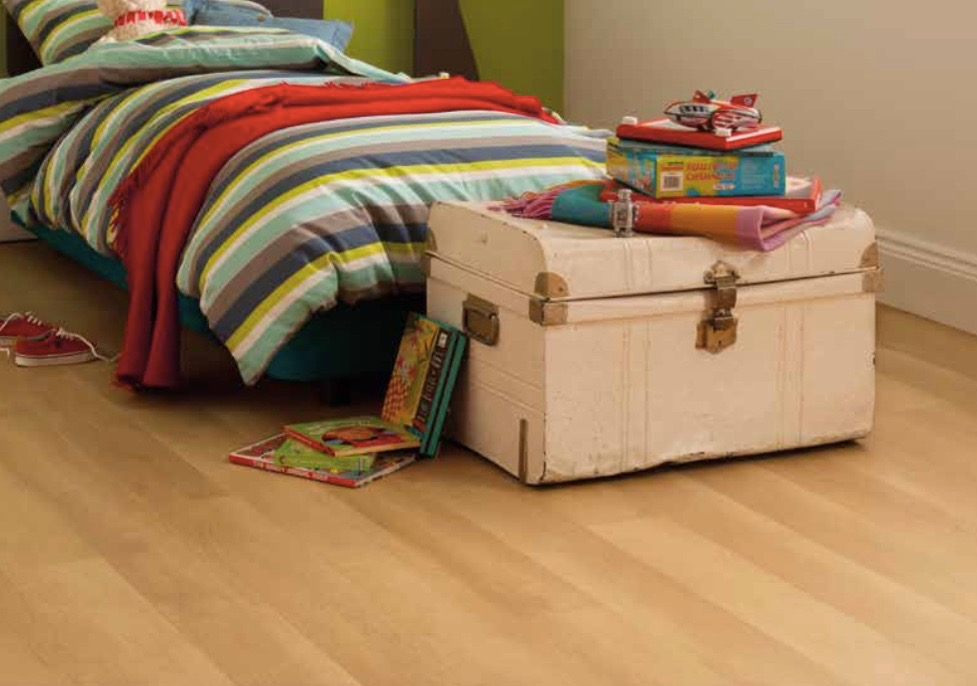 White childrens bedroom with a stripy bed wooden flooring and a toy chest with toys stacked on top