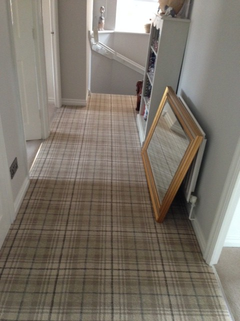 Beige Tartan carpet in a hallway above some stairs with grey walls