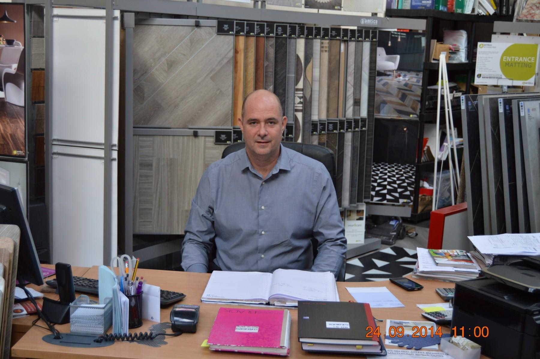 Man sat at a desk with various flooring samples behind him
