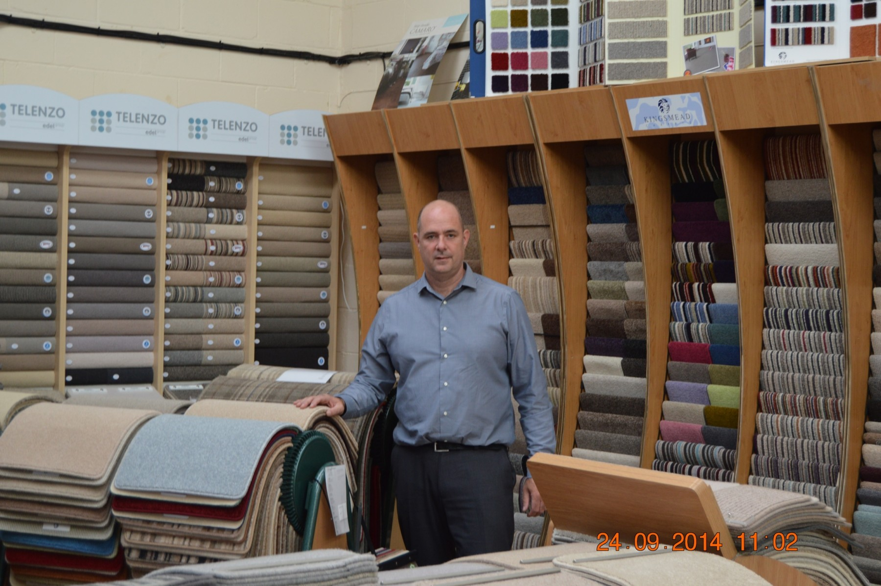 Man stood in a carpet showroom with the date in the bottom right