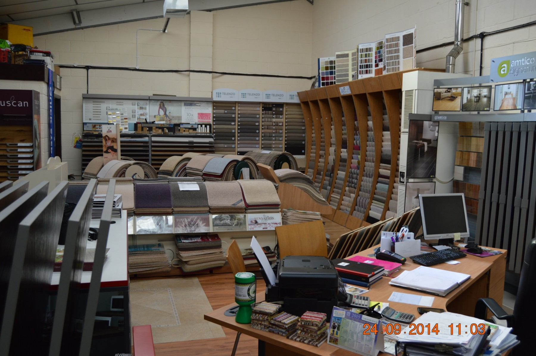 Flooring showroom with different styles of carpet and a wooden desk