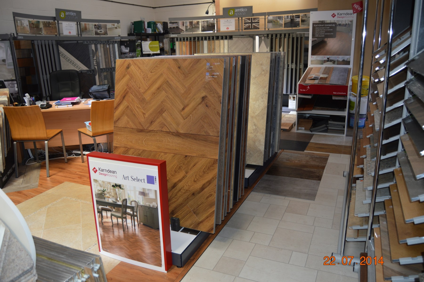 Flooring showroom with different types of wooden flooring and a desk to the left