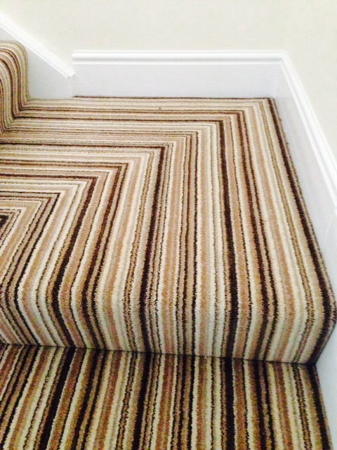 Striped carpet on a corner stair case with cream walls