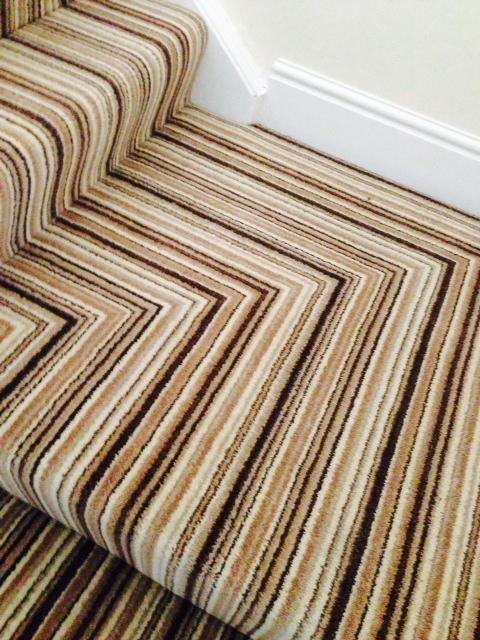 Striped carpet on a corner stair case