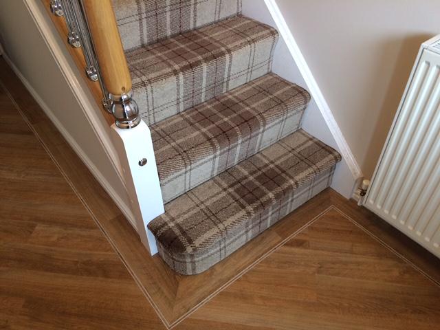 Tartan style carpet stairs with wooden flooring below