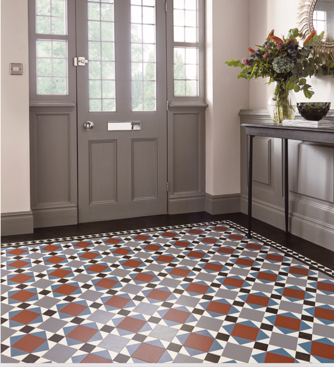 Hallway with a grey front door with large windows, grey furniture and a patterned red blue and white floor