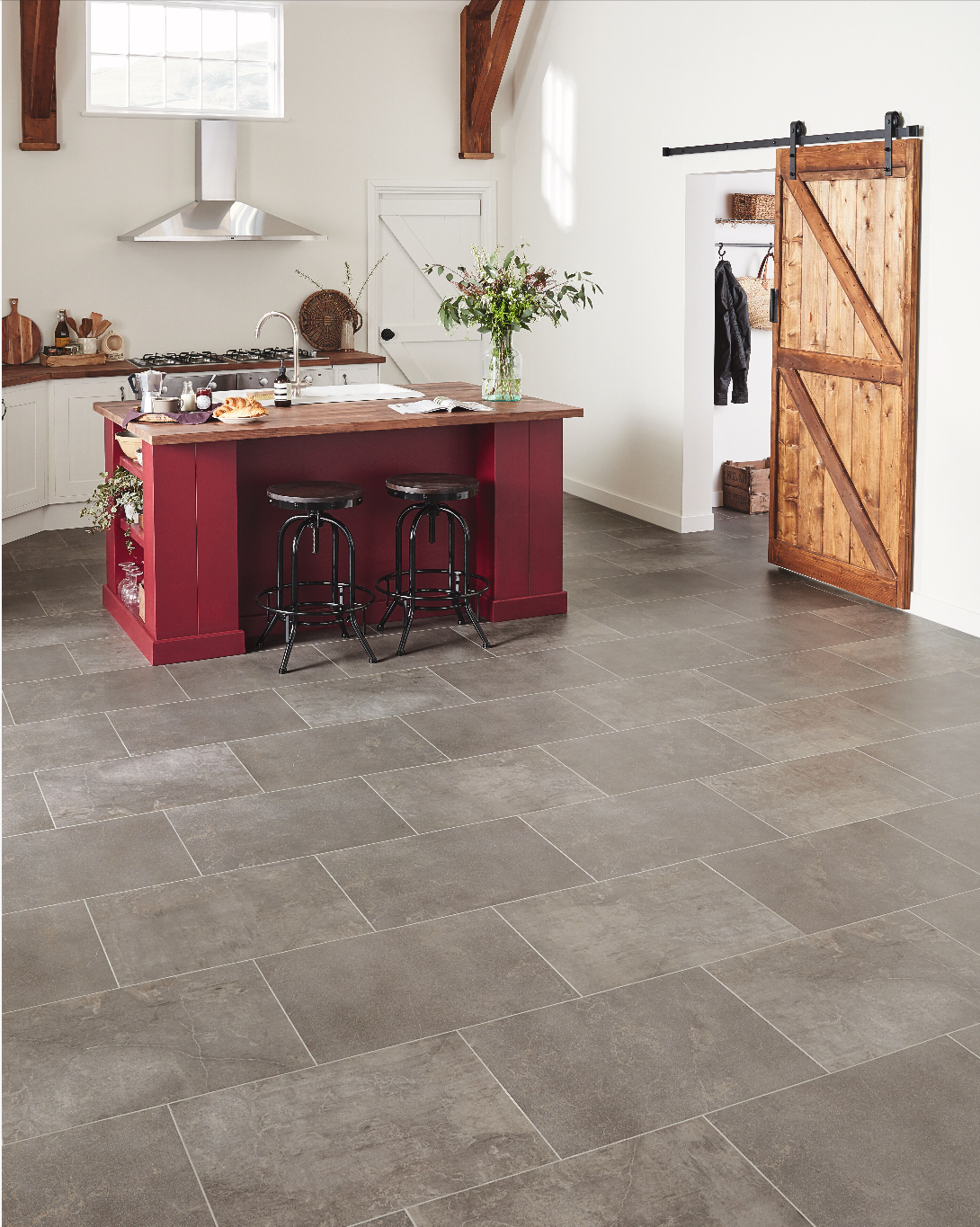 White kitchen with grey tile flooring a red island and wooden features