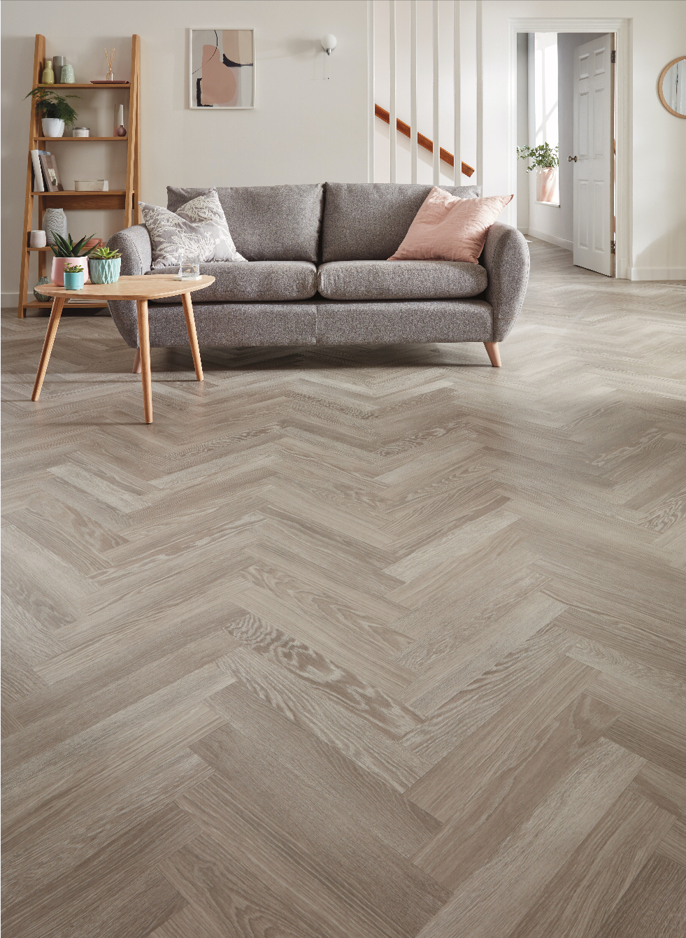 Cream room with chevron flooring a grey couch and wooden furniture